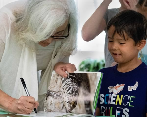 Marta signing Anoles Invasion book for child